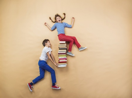 Foto de Happy children playing with group of books in studio - Imagen libre de derechos