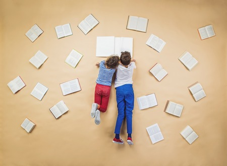 Photo pour Happy children are reading book on the floor with group of books around them - image libre de droit