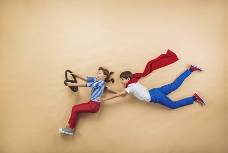 Photo pour Funny children are playing together. Lying on the floor. - image libre de droit