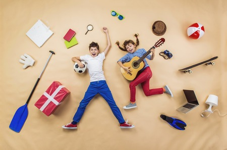 Photo pour Funny children are playing together. Lying on the floor with guitar and ball - image libre de droit