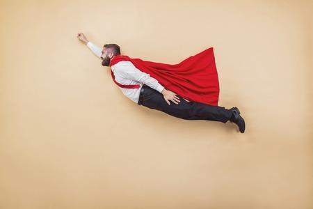 Foto de Manager in a flying pose wearing a red cloak. Studio shot on a beige background. - Imagen libre de derechos