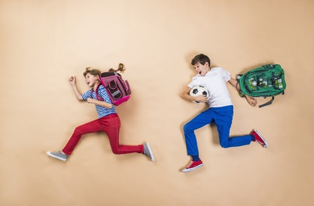 Foto de Happy children running to school in a hurry. Studio shot on a beige background. - Imagen libre de derechos