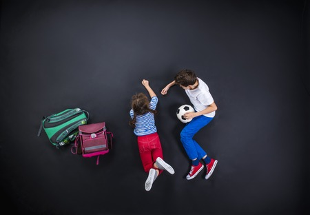 Photo pour Playful young siblings having fun together as they prepare to go back to school. Studio shot on a black background. - image libre de droit