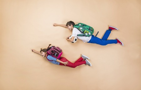 Foto für Happy children running to school in a hurry. Studio shot on a beige background. - Lizenzfreies Bild