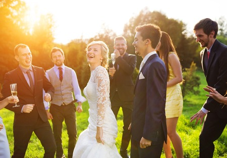 Photo for Full length portrait of newlywed couple dancing and having fun with bridesmaids and groomsmen in green sunny park - Royalty Free Image