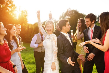 Photo pour Full length portrait of newlywed couple dancing and having fun with bridesmaids and groomsmen in green sunny park - image libre de droit
