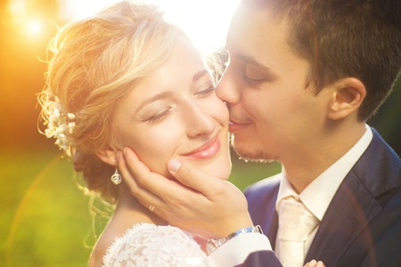 Photo pour Young wedding couple enjoying romantic moments outside on a summer meadow - image libre de droit
