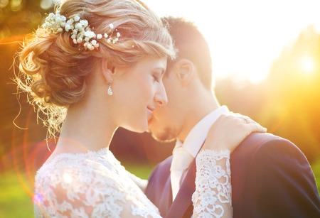 Foto de Young wedding couple enjoying romantic moments outside on a summer meadow - Imagen libre de derechos
