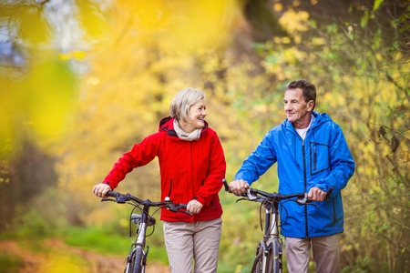 Foto de Active seniors having walk with bike in autumn nature. They having romantic time outdoor. - Imagen libre de derechos
