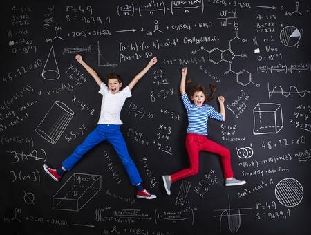 Foto de Cute boy and girl learning playfully in frot of a big blackboard - Imagen libre de derechos