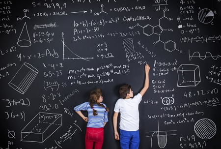 Foto de Cute boy and girl learning playfully in frot of a big blackboard - Imagen libre de derechos
