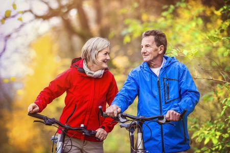 Photo for Active seniors having walk with bike in autumn nature. They having romantic time outdoor. - Royalty Free Image