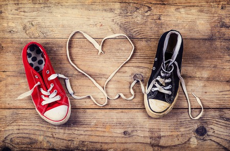 Photo pour Original Valentine\'s Day love concept with red and black sneakers. Studio shot on a wooden floor background. - image libre de droit