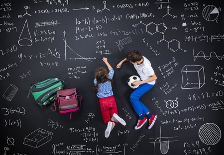 Photo pour Cute boy and girl learning playfully in frot of a big blackboard - image libre de droit