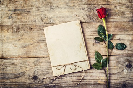 Photo for Valentine´s day composition of a love journal and a red rose. Studio shot on a wooden floor background. - Royalty Free Image