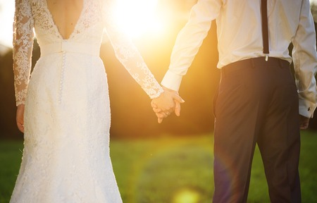 Photo pour Young wedding couple holding hands as they enjoy romantic moments outside on a summer meadow - image libre de droit