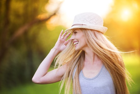 Photo pour Attractive young woman enjoying her time outside in park with sunset in background. - image libre de droit