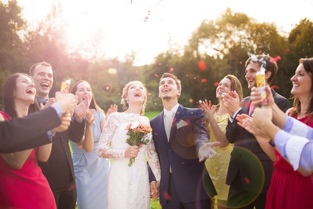 Photo for Full length portrait of newlywed couple and their friends at the wedding party showered with confetti in green sunny park - Royalty Free Image