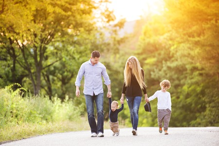 Photo pour Happy young family walking down the road outside in green nature. - image libre de droit