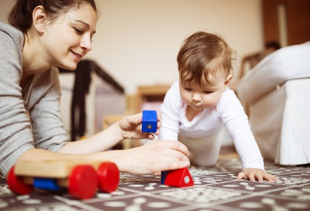 Photo pour Cute little baby girl playing with her mother on a carpet in a living room. - image libre de droit