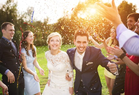 Foto de Full length portrait of newlywed couple and their friends at the wedding party showered with confetti in green sunny park - Imagen libre de derechos