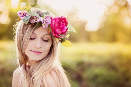 Photo pour Attractive young woman with flower wreath on her head with sunset in background. - image libre de droit