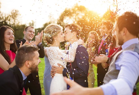 Photo pour Full length portrait of newlywed couple and their friends at the wedding party showered with confetti in green sunny park - image libre de droit