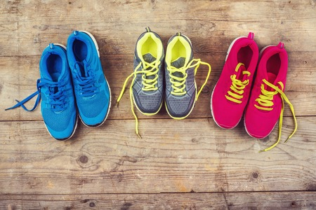 Photo pour Various pairs of colorful sneakers laid on the wooden floor background - image libre de droit