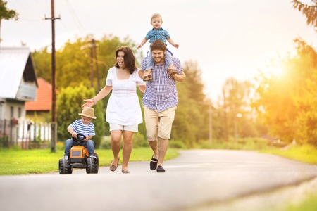 Photo for Happy young family having fun outside on the street of a village - Royalty Free Image