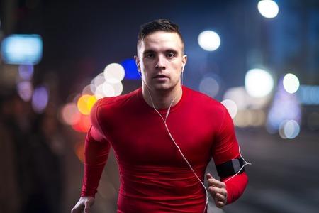 Photo pour Young sportsman jogging in the night city - image libre de droit