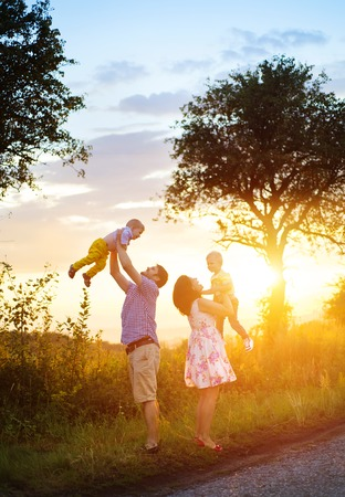 Foto de Happy young family spending time together outside in green nature. - Imagen libre de derechos