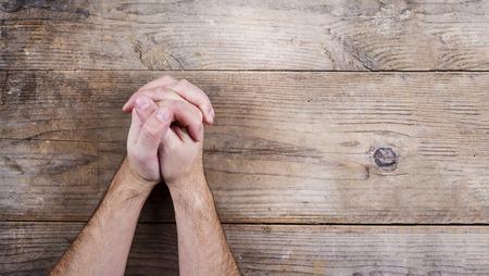 Photo pour Hands of praying young man on a wooden desk background. - image libre de droit