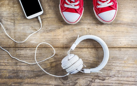Photo for Concept with red sneakers and tablet with white headphones laid on wooden floor background. - Royalty Free Image