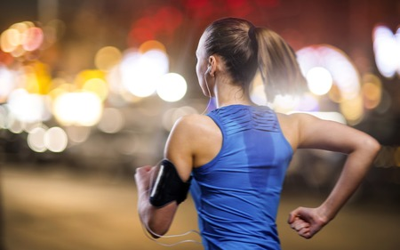 Photo pour Young woman jogging at night in the city - image libre de droit