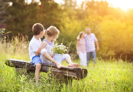 Foto per Happy young family spending time together outside in green nature. - Immagine Royalty Free