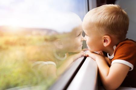 Photo pour Little boy traveling in train looking outside the window. - image libre de droit