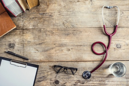 Photo for Workplace of a doctor. Stethoscope, clip board, books, glasses and other things on wooden desk background. - Royalty Free Image