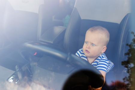 Little boy playing with a steering wheel in a car