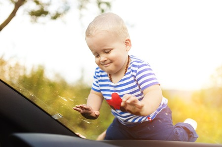 Little boy playing on a windshield of a car