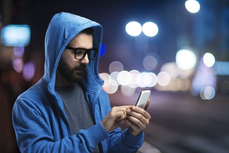 Foto de Handsome young hipster with his smartphone outside in the night city - Imagen libre de derechos
