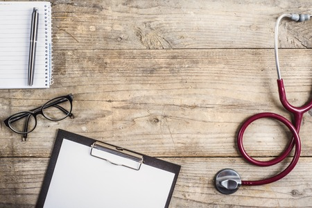 Foto de Workplace of a doctor. Stethoscope, clip board, glasses and other things on wooden desk background. - Imagen libre de derechos