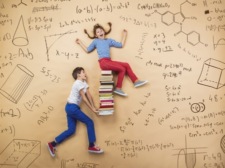 Photo pour Cute boy and girl learning playfully in frot of a big blackboard. Studio shot on beige background. - image libre de droit