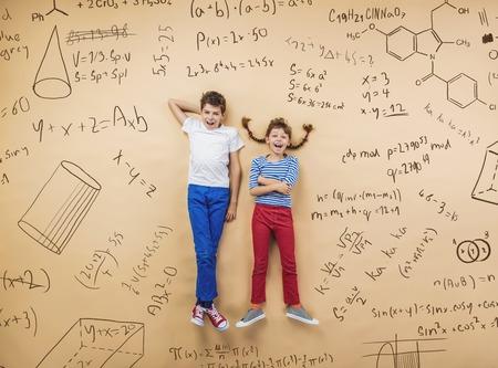 Foto de Cute boy and girl learning playfully in frot of a big blackboard. Studio shot on beige background. - Imagen libre de derechos