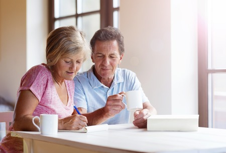 Foto de Happy senior couple sitting at the table making plans and drinking coffee in their living room. - Imagen libre de derechos