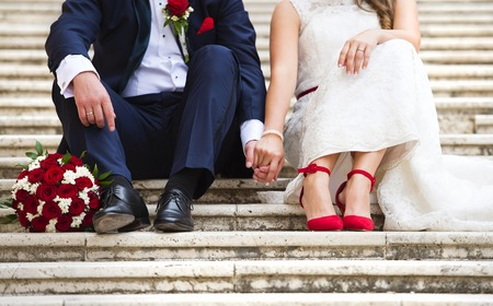 Foto de Unrecognizable young wedding couple holding hands as they enjoy romantic moments outside on the stairs - Imagen libre de derechos