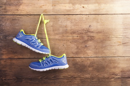 Photo pour Pair of sneakers hang on a nail on a wooden fence background - image libre de droit
