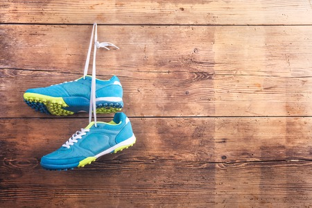 Photo pour Pair of sports shoes hang on a nail on a wooden fence background - image libre de droit