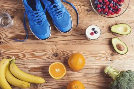 Foto de Pair of running shoes and healthy food composition on a wooden table background - Imagen libre de derechos