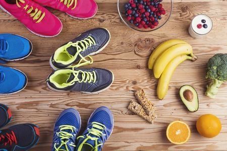 Photo pour Running shoes and healthy food composition on a wooden table background - image libre de droit