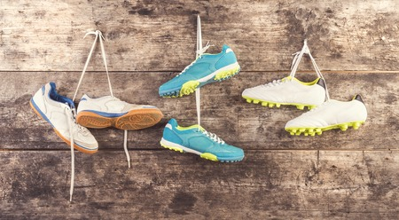 Photo pour Three pairs of sports shoes hang on a nail on a wooden fence background - image libre de droit